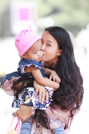 Asian woman holding and kissing her daughter on cheek photo