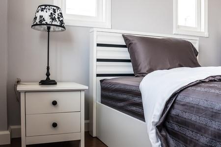 Bed met zwart laken en lamp in witte slaapkamer