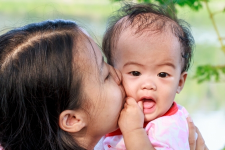Asian woman holding and kissing her daughter photo