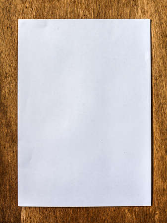 Blank white paper on brown plywood surface photo