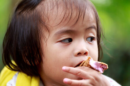 comiendo helado: Beb� asi�tico comer helado en el parque Foto de archivo