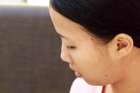 Distracted face of Asian woman close up photo