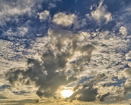 Sun behind clouds with blue sky background