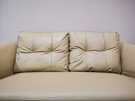Brown polyurethane seat with two pillows close up