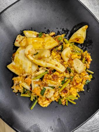 Thai cuisine stir squid in salted egg yolk sauce on black dish Stock Photo