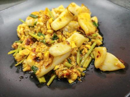 Thai cuisine stir squid in salted egg yolk sauce on black dish 写真素材