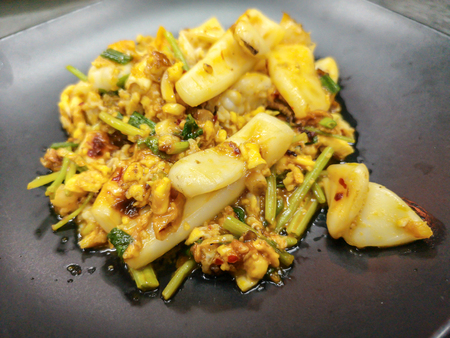 Thai cuisine stir squid in salted egg yolk sauce on black dish Imagens - 105929054