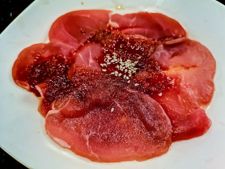 Sliced uncooked raw pork on white dish