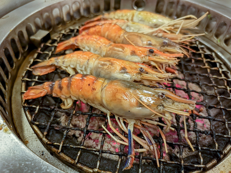 Cooking by grilling prawn on charcoal barbecue stove