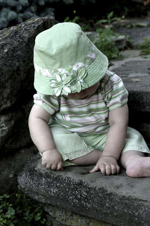 adorable camera shy baby sitting on step