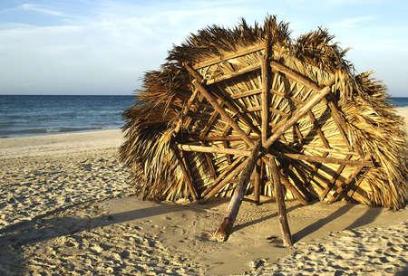 fallen beach cabana buried in sand