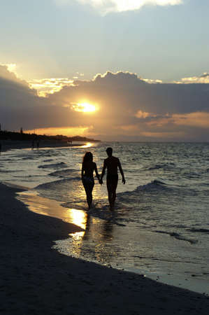 Lovers walking the beach at sunset
