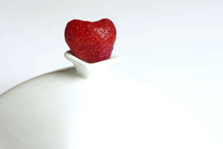 heart shaped: heart shaped strawberry sitting on perch