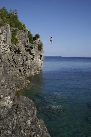 jumping off cliff into the water Stock Photo