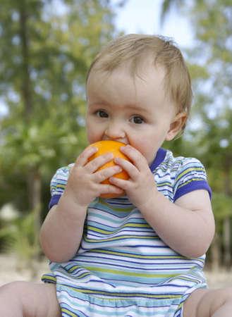 cute  biting into orange Stock Photo