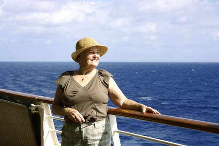 senior lady looking over balcony on cruise ship Stock Photo