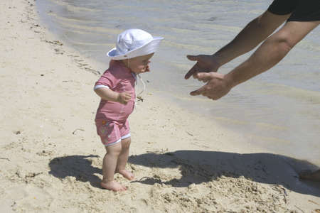 young daughter walking to daddy for first beach experience