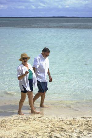 happy attractive senior couple walking on beach