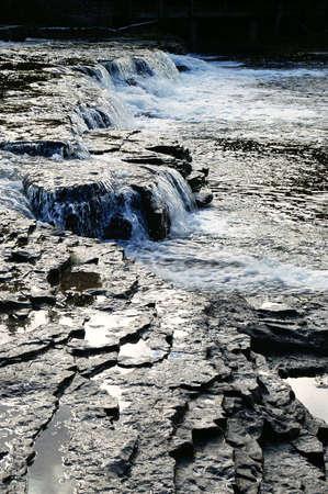 watering flowing over the dark rocks of rapids Stock Photo