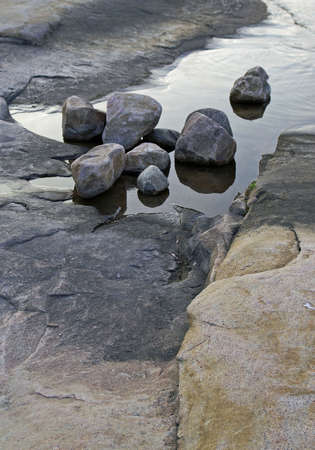 Rounds rocks sit on top of flat rocks and water Stock Photo