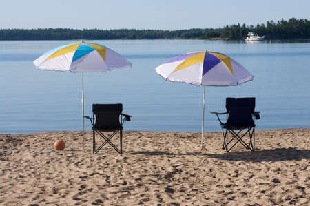 two beach umbrellas and chairs in the sand at the lake