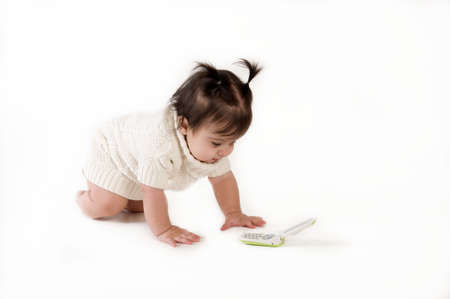 adorable baby girl crawling to phone