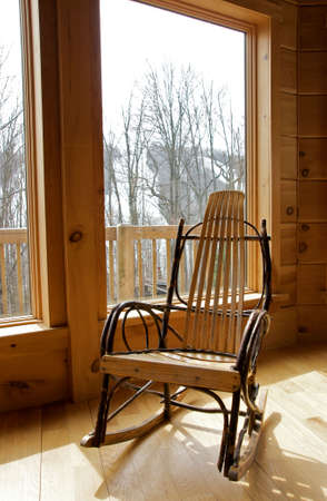 rustic wood rocking chair by window Stock Photo