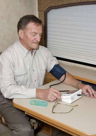senior man checking his blood pressure with home testing ket photo