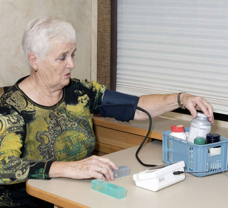 senior woman checking blood pressure results and looking at pills photo
