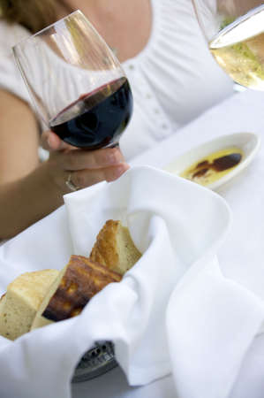 bread basket at a table setting with oil and wine