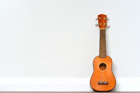 small orange Ukelele leaning on white wall