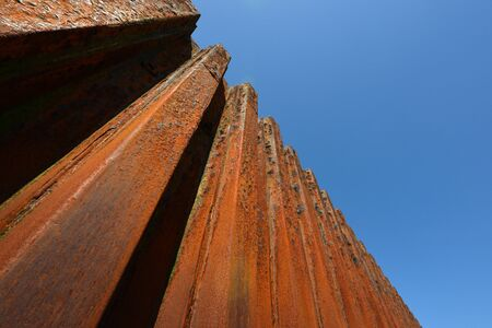 impenetrable: Rusty metal groynes in sea defense wall Stock Photo