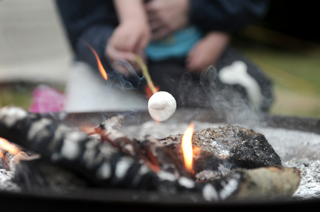 Roasting marshmallows over an open camp fire