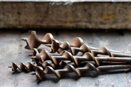 augers: Old hand drill bits in a workshop, augers Stock Photo