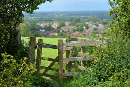 english oak: Gate or style overlooking typical English country village, Sussex Stock Photo