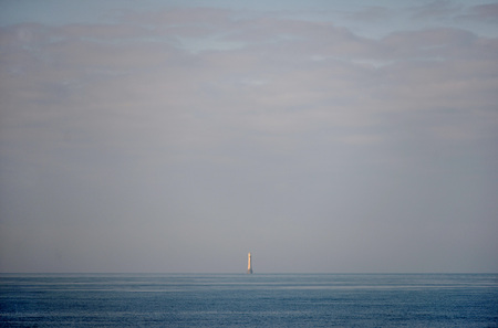 bleak: Distant offshore lighthouse in blue sea and sea mist Stock Photo