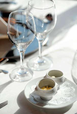 restaurant setting: Butter portions and wine glasses in restaurant setting