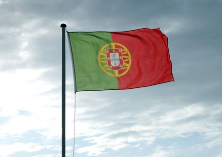 lit: back lit portuguese flag flying on flag pole Stock Photo