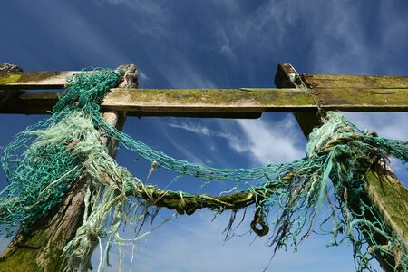 groynes: Old fishing nets caught up on wooden groynes