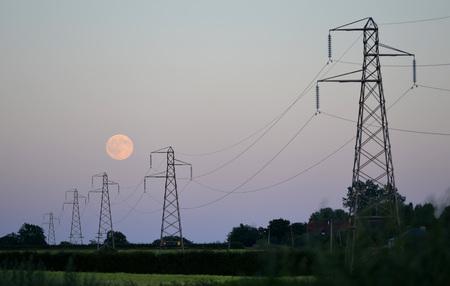 torres de alta tension: luna llena detrás de la fila de torres de alta tensión Foto de archivo