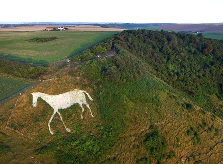 Aerial shot of white horse carved into the chalk at High and Over, South Downs National Park