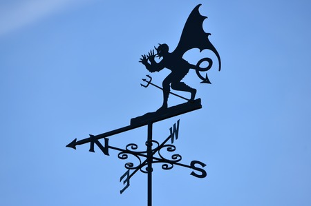 winged Devil or demon weather vane with blue sky Stock Photo