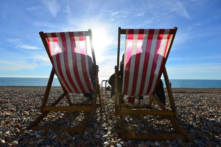 Deck chairs and sun on a stony beach