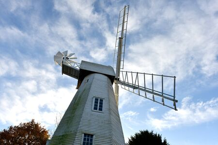 sweeps: White wooden windmill in front of blue sky