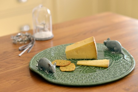Cheese on a green embossed plate with ceramic mouse