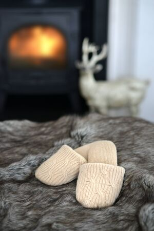 Woolen slippers n front of a log burning stove