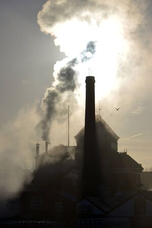 Steam rising from an old brewery chimney stack