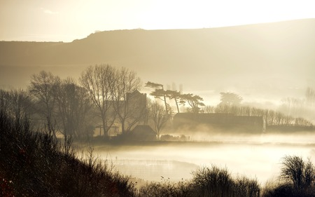 Morning mist surrounding a british church and trees Stock Photo