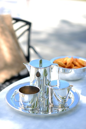 aspirational: Luxury silver coffee pot on a linen covered table outside in summer.