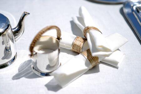napkin ring: White linen napkins in silver and wicker napkin rings